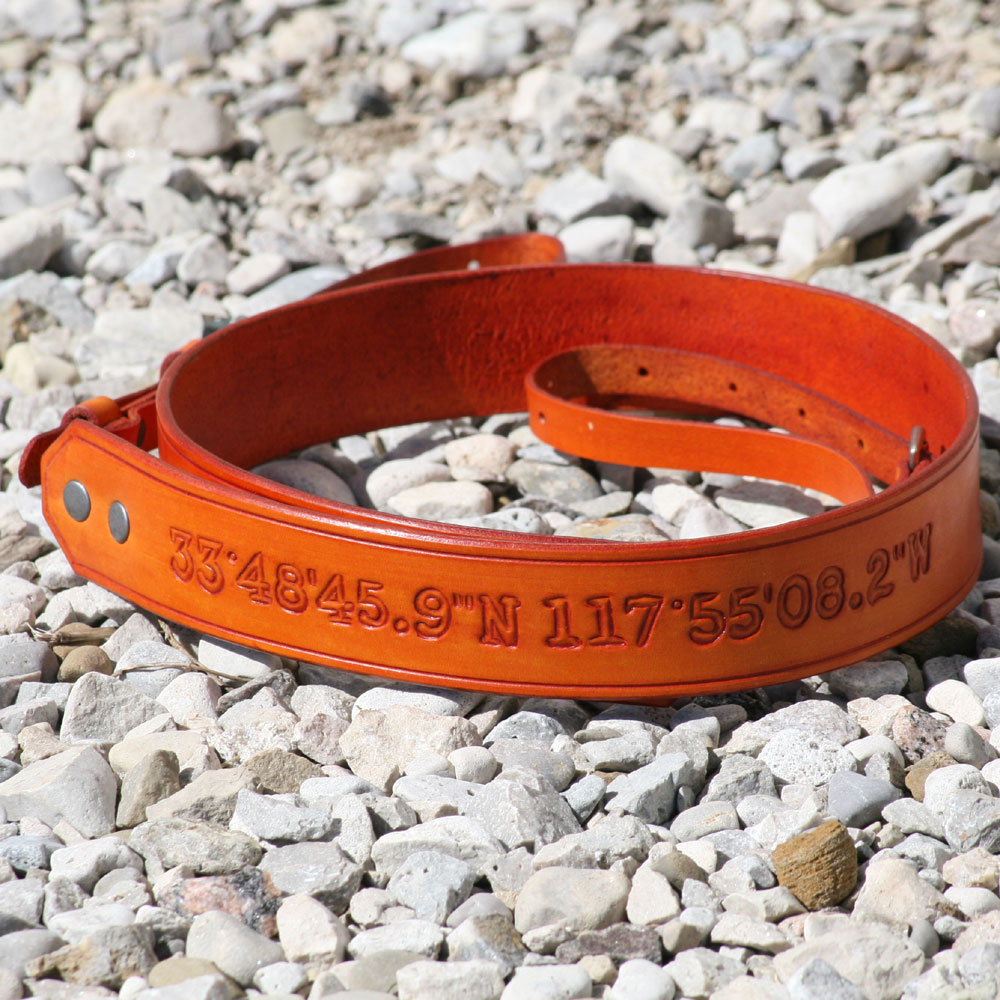 co-ordinates hand carved into this orange neck strap